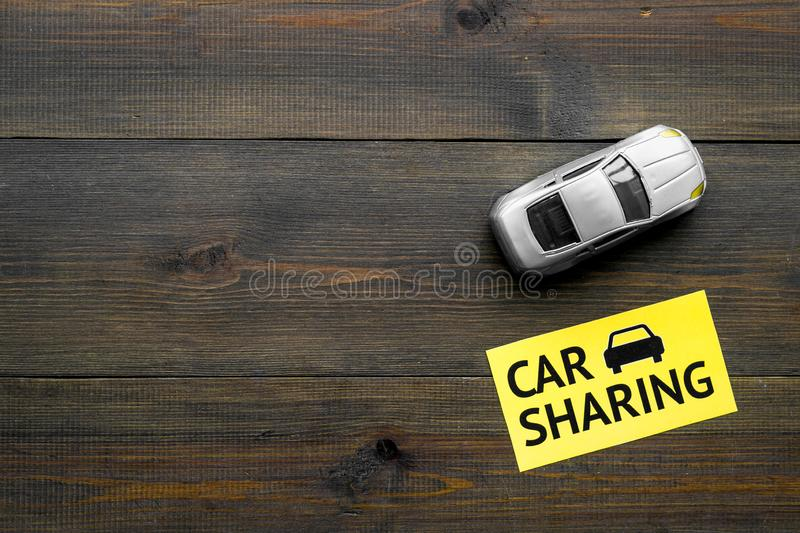 Carsharing concept. Toy car near text car sharing on dark wooden background top view space for text. Carsharing concept. Toy car near text car sharing on dark stock photo