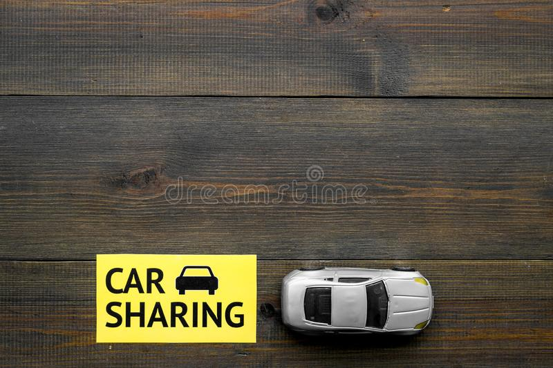 Carsharing concept. Toy car near text car sharing on dark wooden background top view space for text. Carsharing concept. Toy car near text car sharing on dark royalty free stock photos