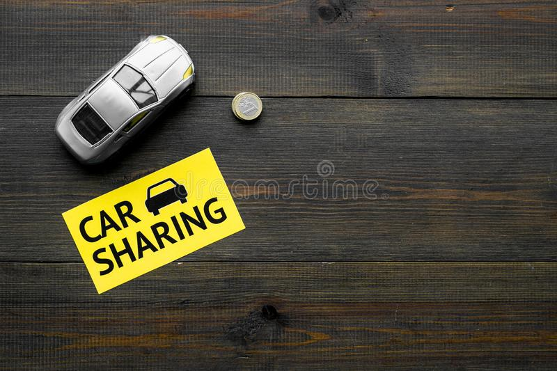 Carsharing concept. Toy car near text car sharing on dark wooden background top view space for text. Carsharing concept. Toy car near text car sharing on dark stock images