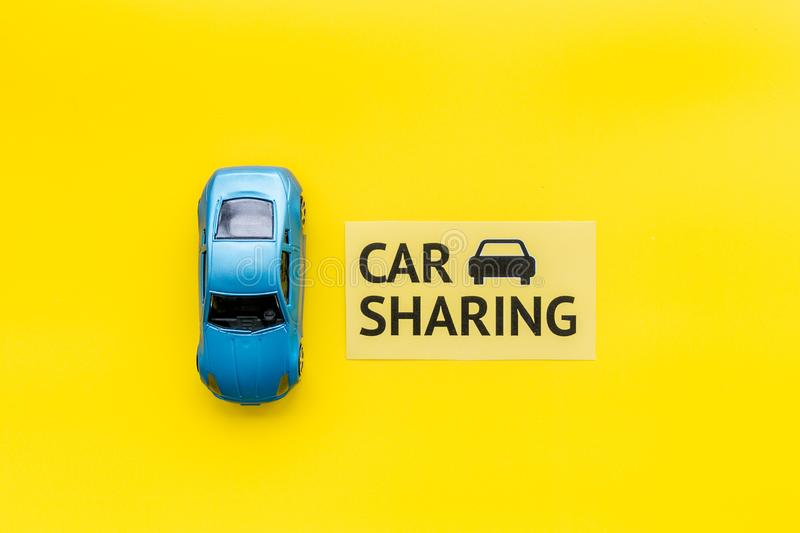 Carsharing concept. Toy car near text car sharing on yellow background top view copy space. Carsharing concept. Toy car near text car sharing on yellow stock photos
