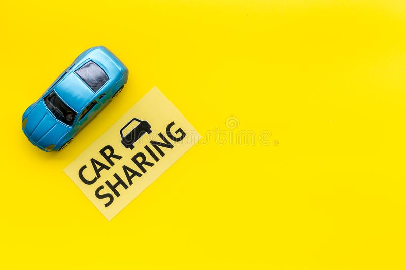 Carsharing concept. Toy car near text car sharing on yellow background top view copy space. Carsharing concept. Toy car near text car sharing on yellow royalty free stock image