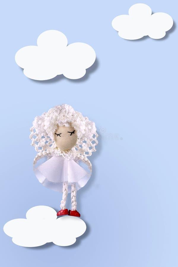 Cartão ascendente trocista com anjo feito a mão bonito na roupa branca em claro - fundo azul nas nuvens brancas Copie o espa?o fotos de stock royalty free
