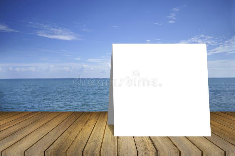 Cartão branco na tabela de madeira vazia e mar bonito da paz no fundo molde da exposição do produto Apresentação do negócio Traje fotografia de stock royalty free