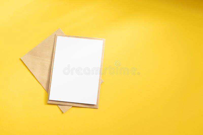 Cartão branco vazio com zombaria de papel marrom do molde do envelope de kraft acima imagem de stock