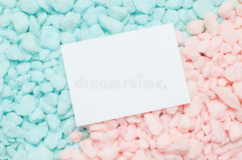 Cartão branco vazio no fundo azul e cor-de-rosa do cascalho fotos de stock