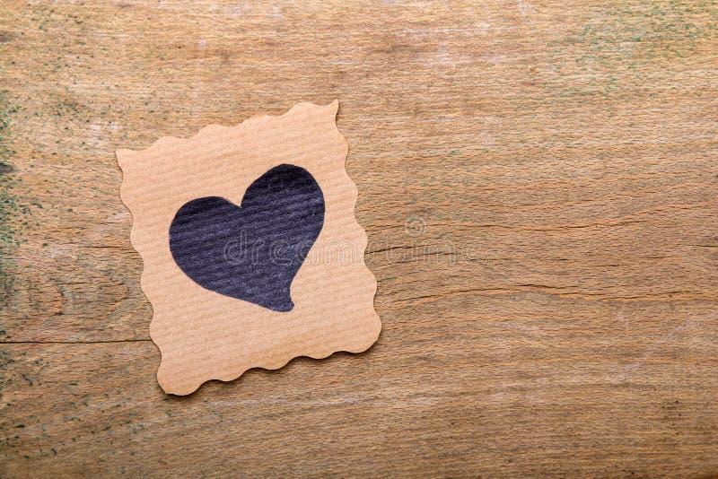 Cartão com o desenho do coração no fundo de madeira foto de stock royalty free