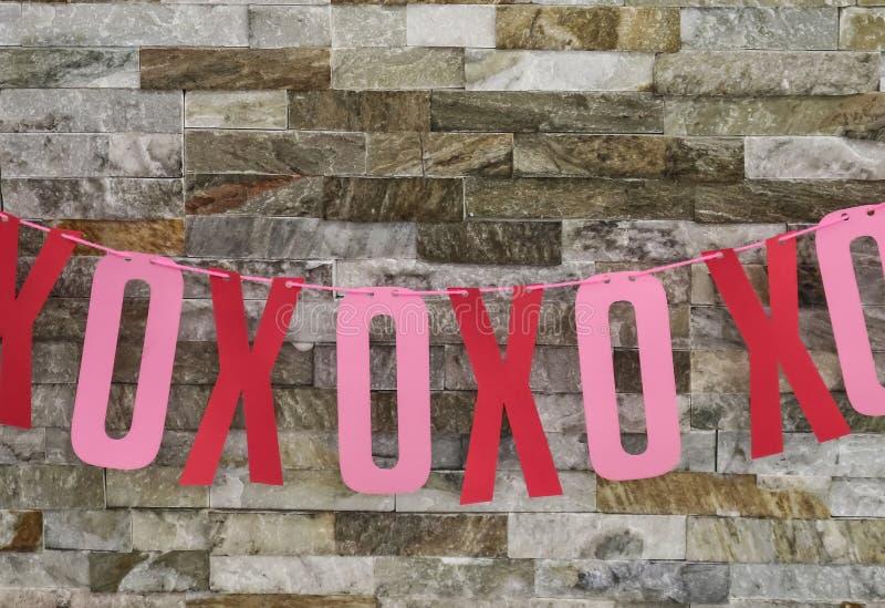 Cartão cortado Xs e ósmio para os abraços e os beijos picados no fio e pendurados na parede da rocha - decoração dos Valentim imagens de stock