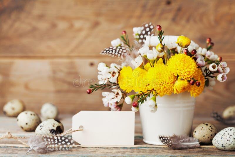 Cartão da Páscoa com flores, a pena e os ovos de codorniz coloridos no fundo de madeira rústico Composição bonita da mola fotografia de stock