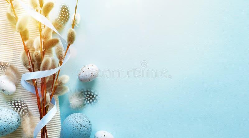 Cartão da Páscoa com ovos da páscoa coloridos e flowersl do sprin na tabela azul Vista superior com espaço para seus cumprimentos fotografia de stock