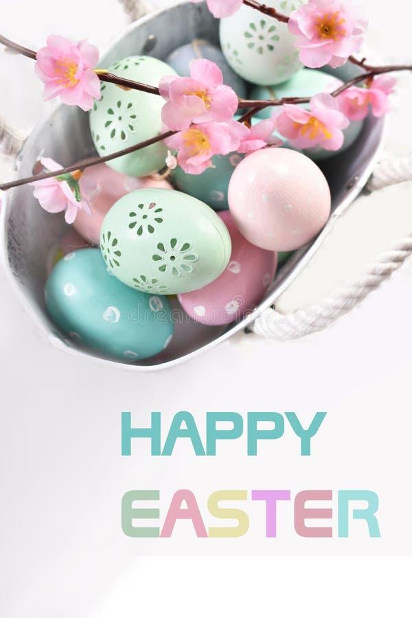 Cartão da Páscoa com texto e os ovos coloridos na cesta do metal foto de stock royalty free