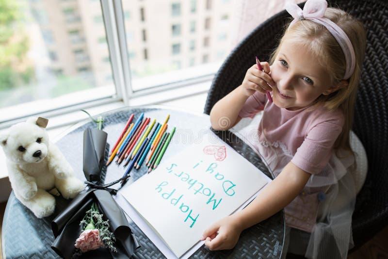 Cartão da pintura da filha da criança para a mamã Menina que senta-se em casa na tabela, flor cor-de-rosa em seguida de encontro  fotografia de stock royalty free