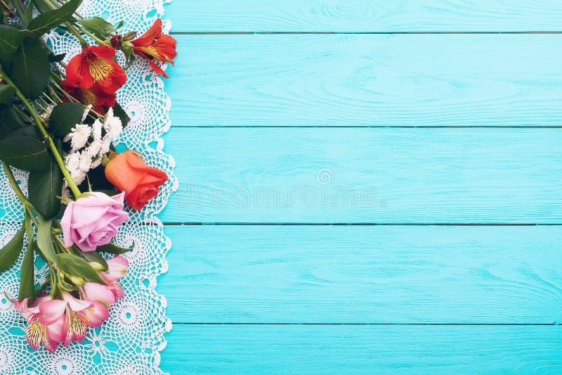 Cartão das flores e da toalha de mesa do laço no fundo de madeira azul Vista superior e foco seletivo Copie o espaço Zombaria aci imagem de stock