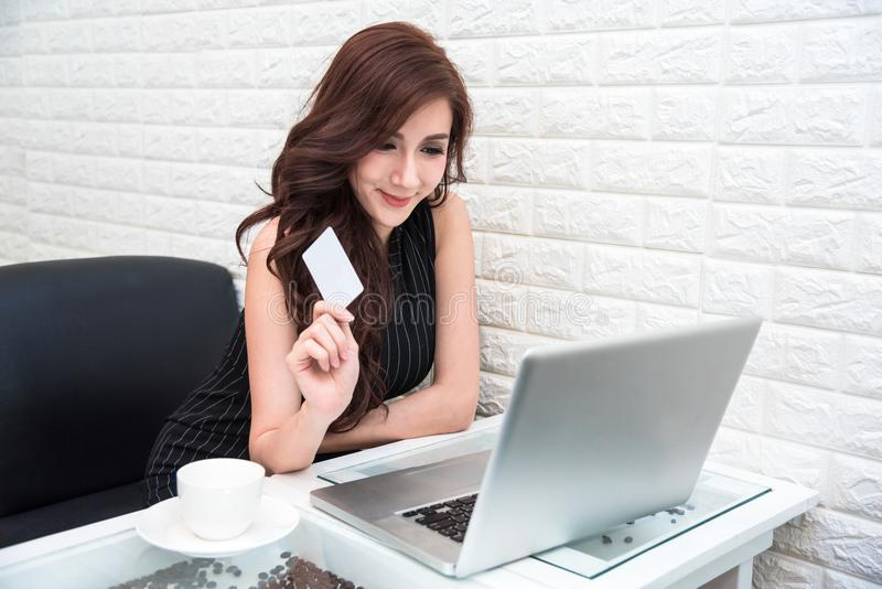 Cartão de crédito asiático novo do uso da mulher para a compra em linha com lapto fotos de stock