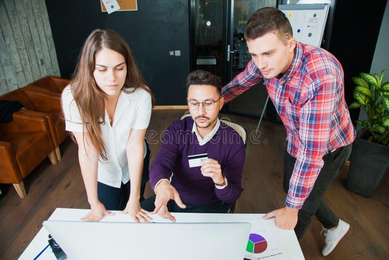 Cartão de crédito da posse da tela de monitor do Internet do relógio de três homens de negócios fotografia de stock