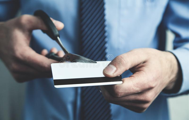 Cartão de crédito do corte do homem de negócios com tesouras fotos de stock royalty free