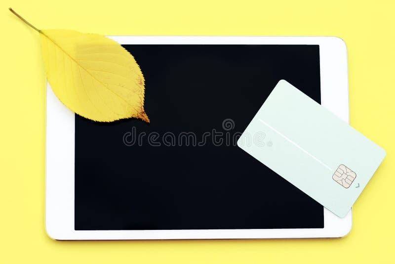 Cartão de crédito e tabuleta em um fundo amarelo, conceito da compra em linha, Cyber segunda-feira foto de stock royalty free