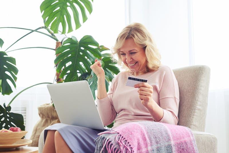 Cartão de crédito guardando fêmea agradável de sorriso ao trabalhar no portátil imagem de stock