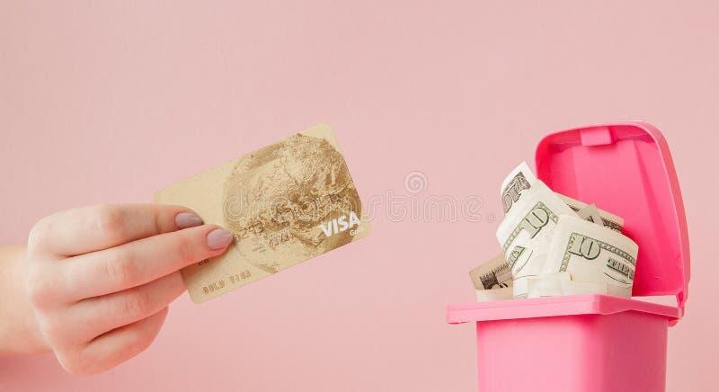 Cartão de crédito na mão de uma mulher e dólares em um balde do lixo no fundo cor-de-rosa imagens de stock royalty free