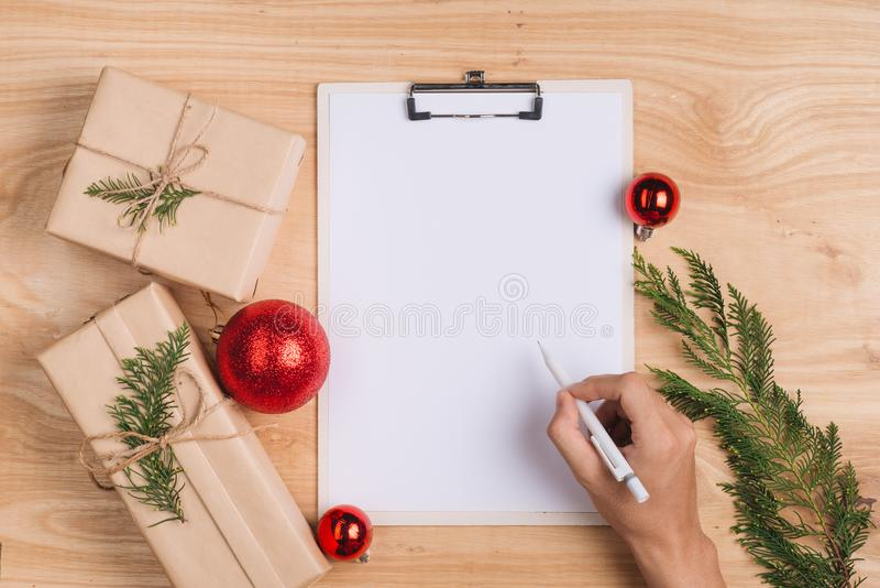 Cartão de escrita masculino do xmas e envolvimento de presentes do Natal A fotografia de stock
