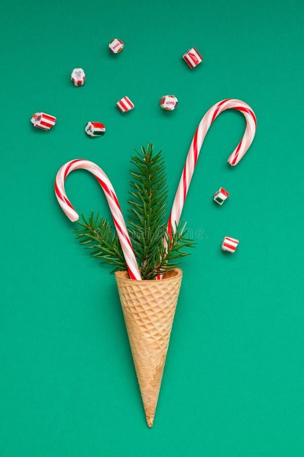Cartão de Natal com os bastões de doces no cone do waffle imagem de stock