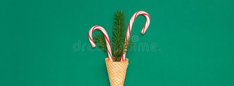 Cartão de Natal com os bastões de doces no cone do waffle fotos de stock