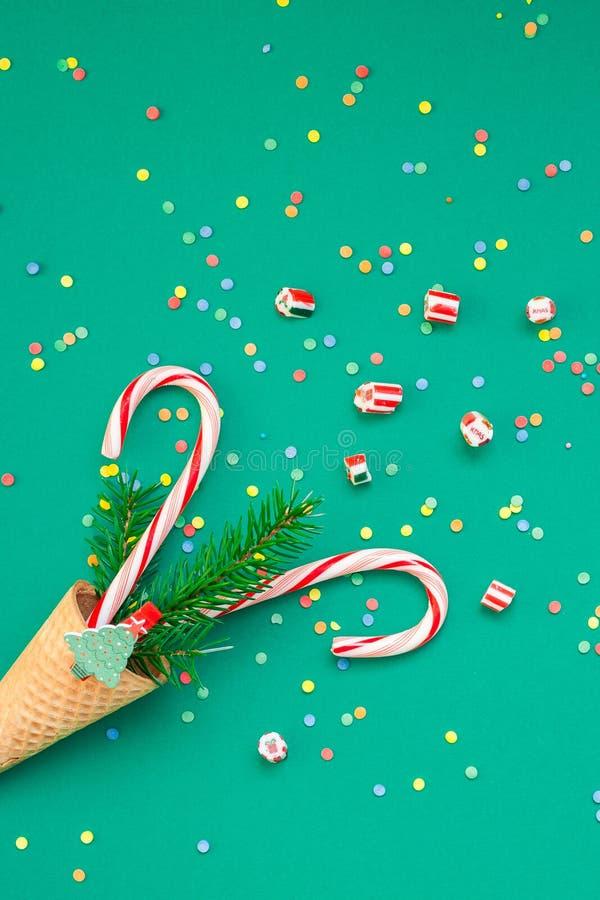 Cartão de Natal com os bastões de doces no cone do waffle imagens de stock royalty free
