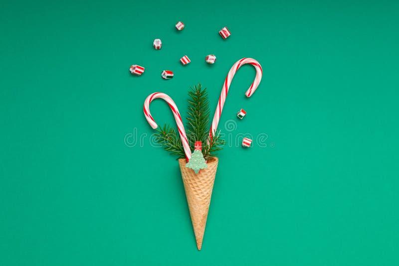 Cartão de Natal com os bastões de doces no cone do waffle foto de stock royalty free