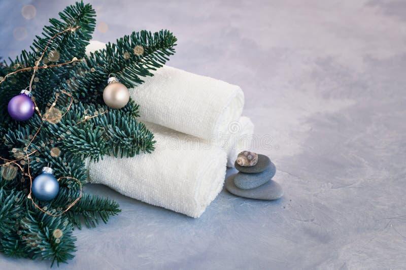 Cartão de Natal e de Ano Novo com ramos de abeto decorados com bolas, luzes, conchas e pedras para tratamentos Spa num imagens de stock