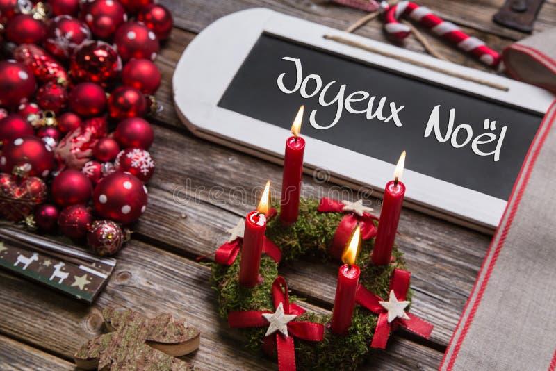 Cartão de Natal francês com quatro velas ardentes vermelhas no vermelho imagem de stock