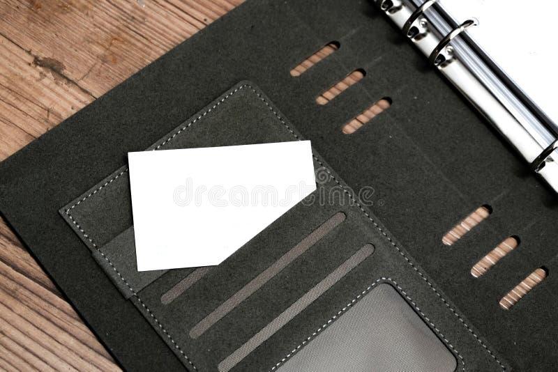 Cartão de nome da vista superior no livro pessoal do planejador, na câmera do vintage e no fundo de madeira do assoalho foto de stock