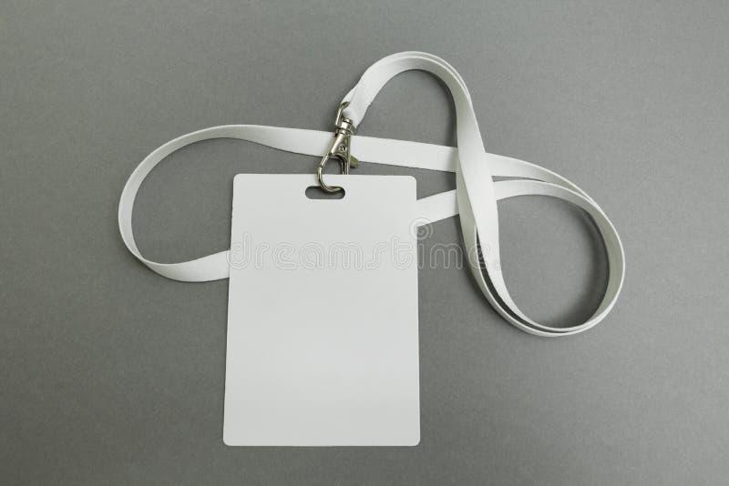 Cartão de nome do homem de negócios em uma correia Etiqueta de identificação isolada no fundo cinzento Cartão em branco da identi imagem de stock