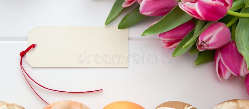 Cartão de Páscoa com o ramalhete de tulipas cor-de-rosa e de ovos coloridos em de madeira branco imagem de stock royalty free