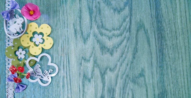 Cartão de Páscoa, em um fundo da madeira azul com flores e decoração fotos de stock royalty free