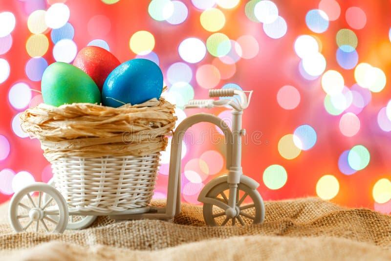 Cartão de Páscoa, ovos coloridos no ninho Toy Bicycle com um carro fotografia de stock royalty free
