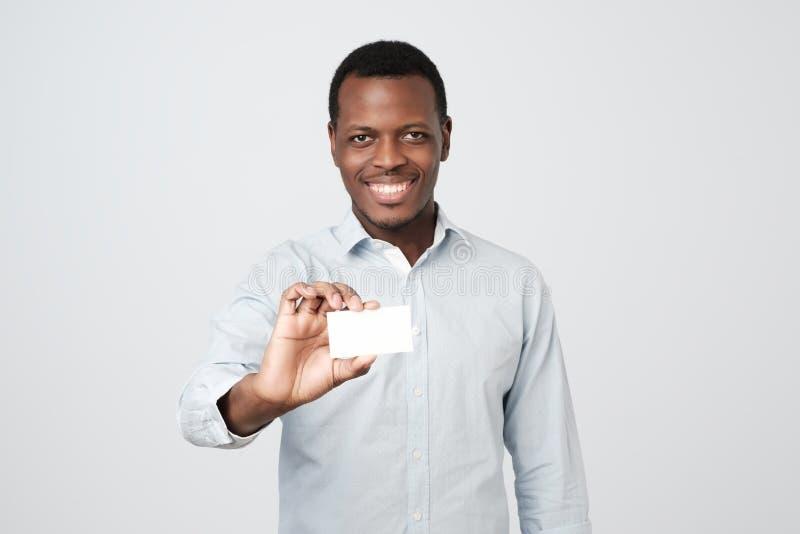 Cartão de visita africano novo do banco da terra arrendada do homem no fundo cinzento foto de stock royalty free