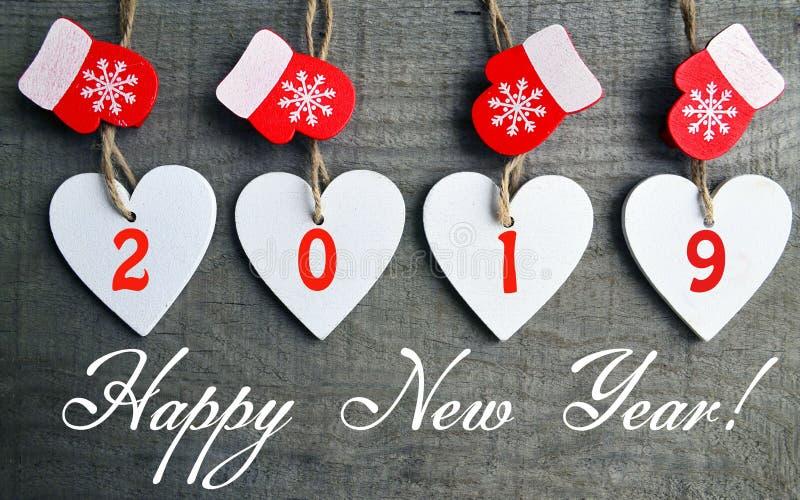 Cartão do ano novo feliz Corações de madeira brancos decorativos do Natal e mitenes vermelhos com 2019 números no fundo de madeir imagens de stock royalty free