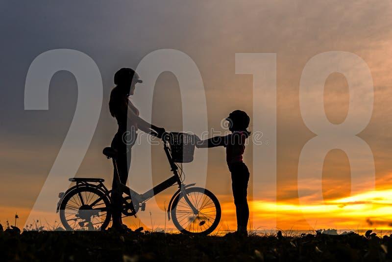 Cartão 2018 do ano novo feliz da família Mostre em silhueta a família bonita do motociclista no por do sol sobre o oceano fotografia de stock