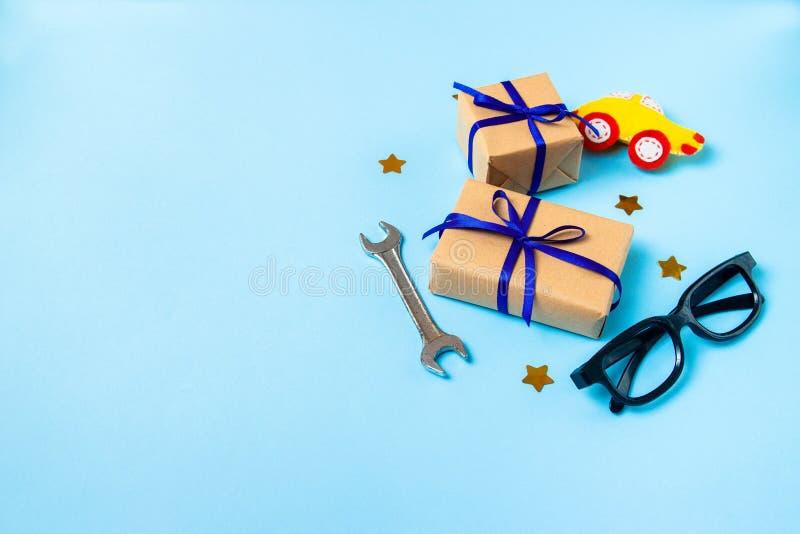 Cart?o do conceito do dia de pai com a ferramenta do trabalho do homem nas caixas azuis do fundo e de presentes envolvidas no pap fotografia de stock royalty free