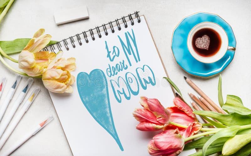 Cartão do dia de mães com o texto que rotula a meus cara mamã, tulipas bonitas, caderno ou bloco de desenho, marcadores coloridos imagens de stock