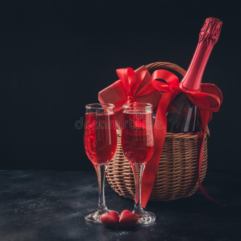 Cartão do dia de Valentim com champanhe e o presente vermelho no preto Espaço para seus cumprimentos imagem de stock