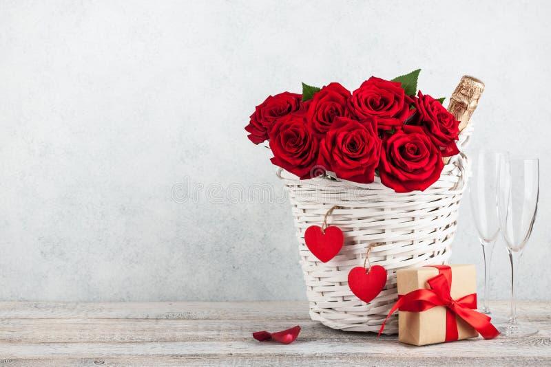 Cartão do dia de Valentim com a garrafa das rosas vermelhas, da caixa de presente e do champanhe fotografia de stock royalty free