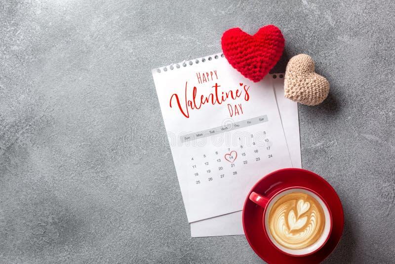 Cartão do dia dos Valentim Copo e caixa de presente de café sobre o calendário de fevereiro na tabela de pedra Vista superior com fotografia de stock royalty free