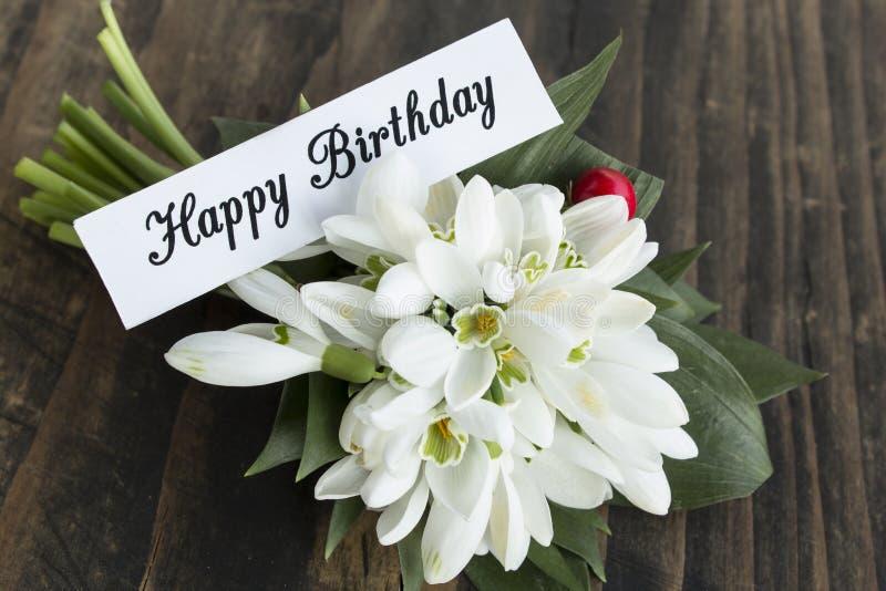 Cartão do feliz aniversario com o ramalhete de Snowdrops fotos de stock royalty free