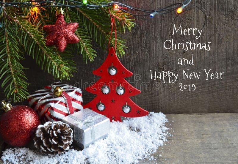Cartão 2019 do Feliz Natal e do ano novo feliz Decoração festiva do inverno com árvore de abeto, luzes da festão e brinquedos foto de stock
