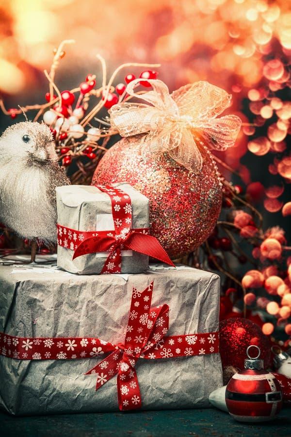 Cartão do Natal com caixas de presente, a bola vermelha da decoração e o pássaro no fundo festivo da iluminação do bokeh, vertica imagens de stock
