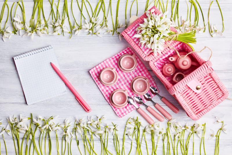 Cartão do piquenique com ajuste da tabela e snowdrops, pratas, guardanapo verificado branco do rosa imagens de stock