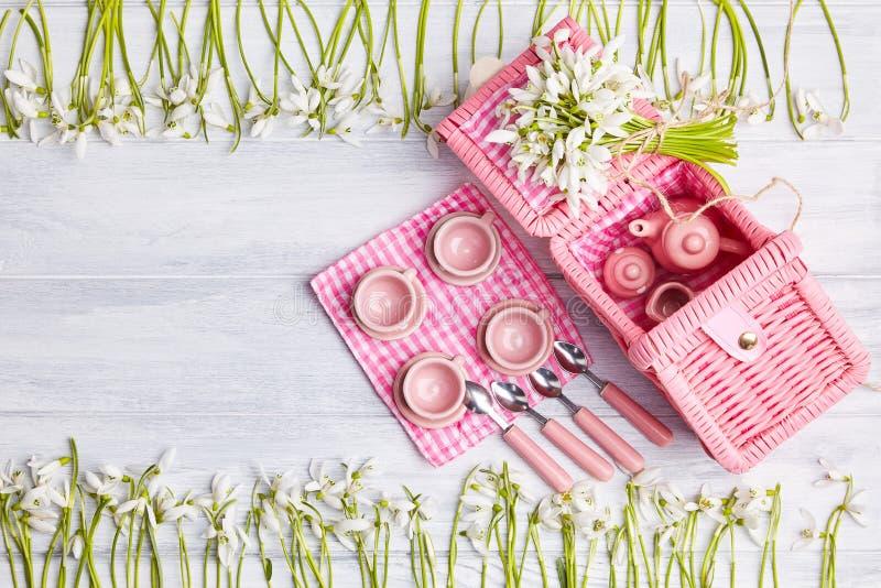 Cartão do piquenique com ajuste da tabela e snowdrops, pratas, guardanapo verificado branco do rosa fotos de stock royalty free