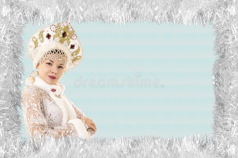 Cartão do projeto-Natal do Natal com uma mulher bonita, nova, sorrindo vestida como Santa Claus, limitada por agulhas do pinho co foto de stock royalty free