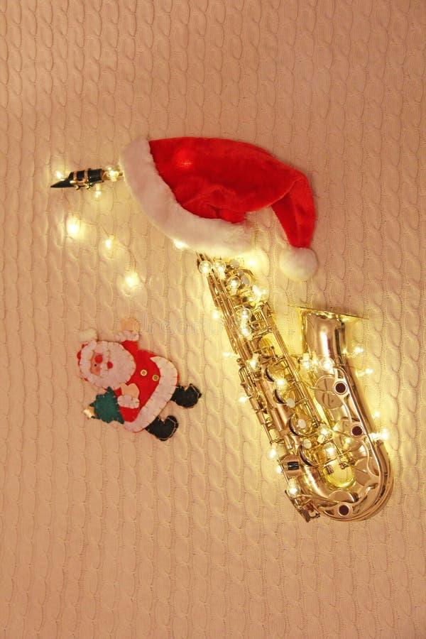Cartão do ` s do ano novo - saxofone, festão, Santa Claus, tampão vermelho imagem de stock