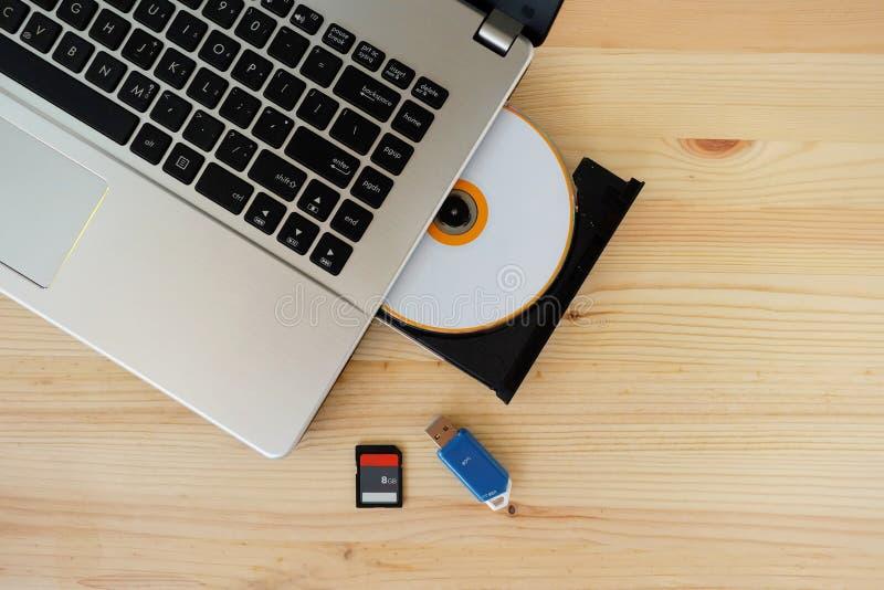 Cartão do SD, movimentação instantânea USB3 0 e escritor Burner Reader da movimentação do CD DVD do laptop no fundo de madeira imagem de stock royalty free
